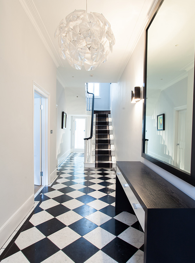 black and white entrance hallway with chequered floor and pendant light