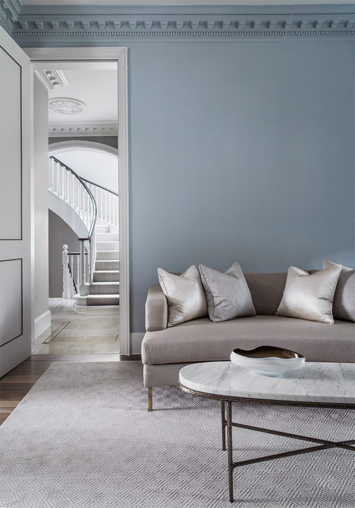 blue living room with bespoke curved sofa and oval marble coffee table