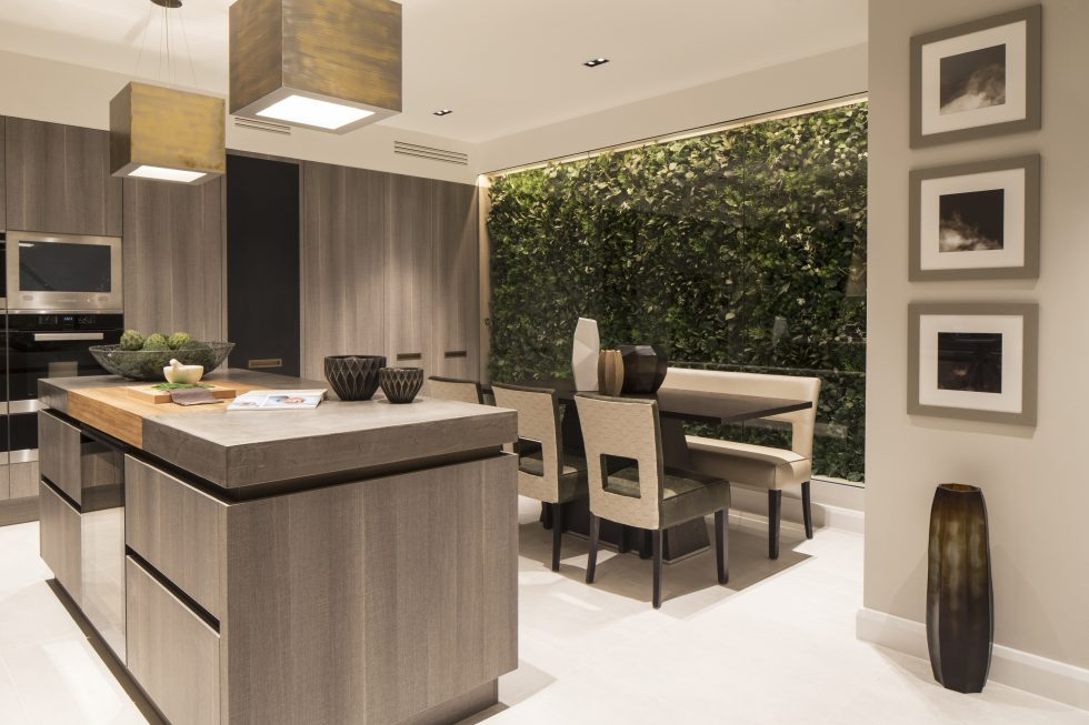 Contemporary basement kitchen with textured surfaces and faux green wall by luxury interior designer Roselind Wilson Design