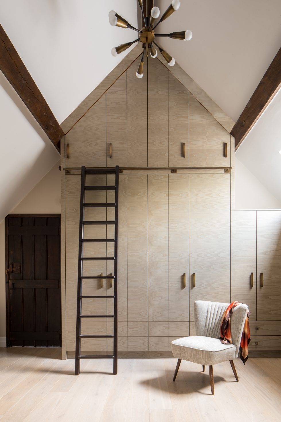 Full-height dressing room joinery storage with dark timber ladder by Roselind Wilson Design