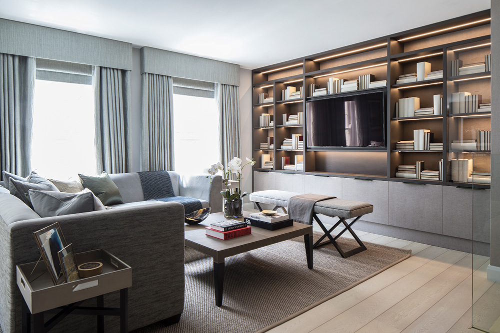 Contemporary grey living room with bespoke joinery shelving and grey L-shaped sofa