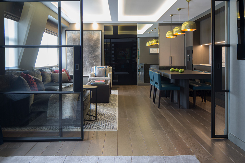 Open plan living room and kitchen with internal pocket doors, bespoke sofa and kitchen island