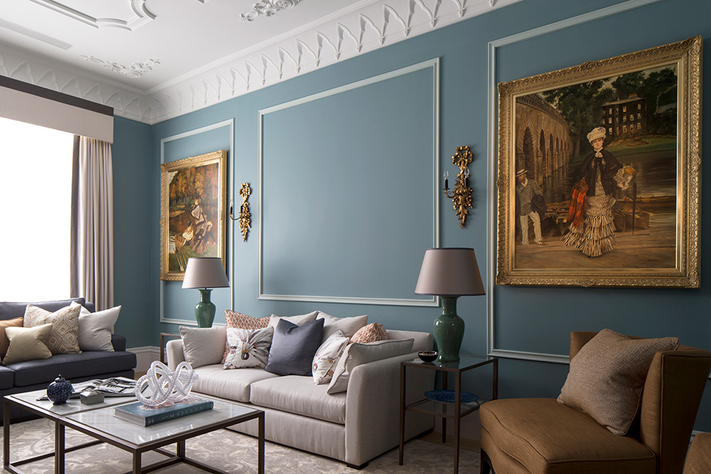 elegant living room with blue walls and gold framed oil paintings