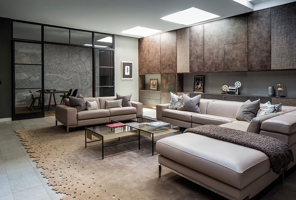 An entertaining room with taupe sofas and brown cupboards