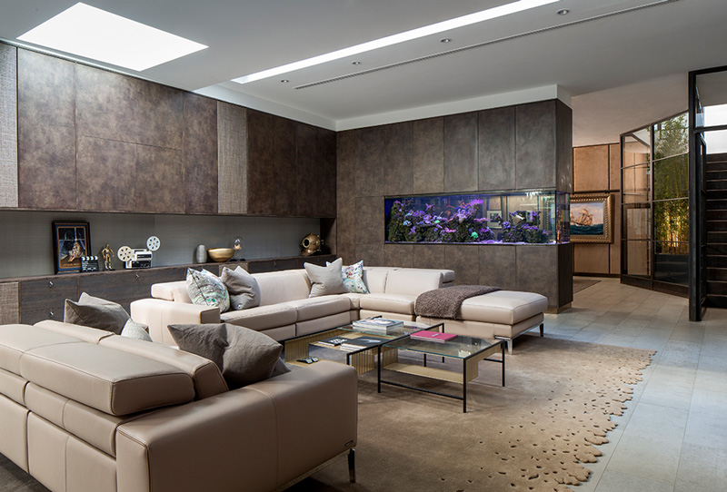 basement living room with bespoke fitted joinery, modern sofas and beige rug
